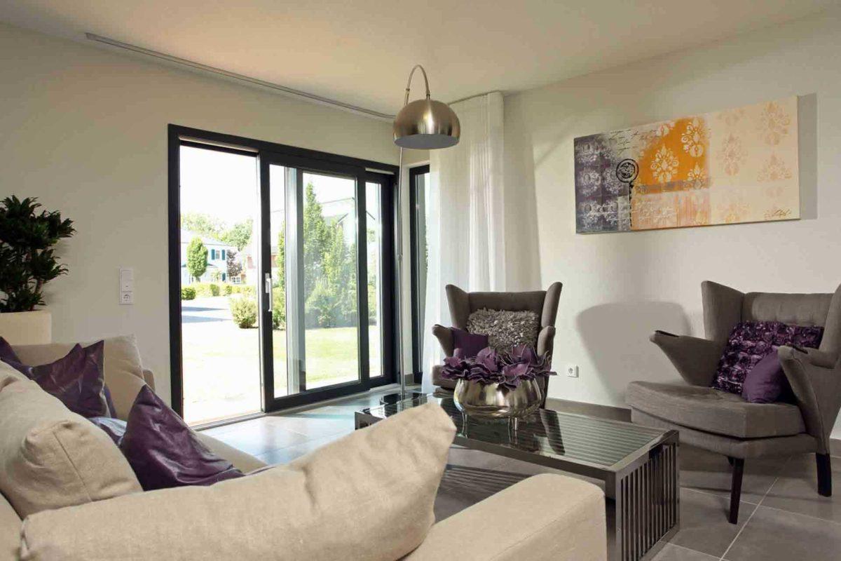 Musterhaus Hannover – NEO 300 - Ein Wohnzimmer mit Möbeln und einem großen Fenster - FingerHaus