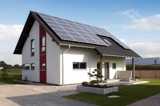 VIO 400 – Musterhaus Köln - Ein großes Backsteingebäude mit Gras vor einem Haus - FingerHaus