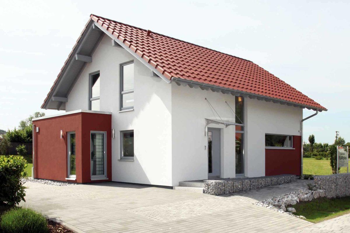 FLAIRplus – Musterhaus Marburg - Ein großes Backsteingebäude mit Gras vor einem Haus - Haus