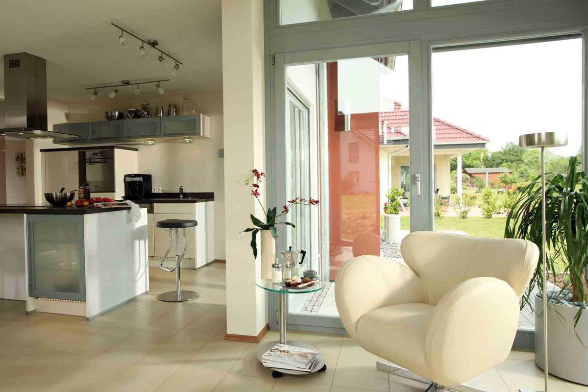 FLAIRplus – Musterhaus Marburg - Ein Wohnzimmer mit Möbeln und einem großen Fenster - FingerHaus GmbH - Musterhaus Marburg