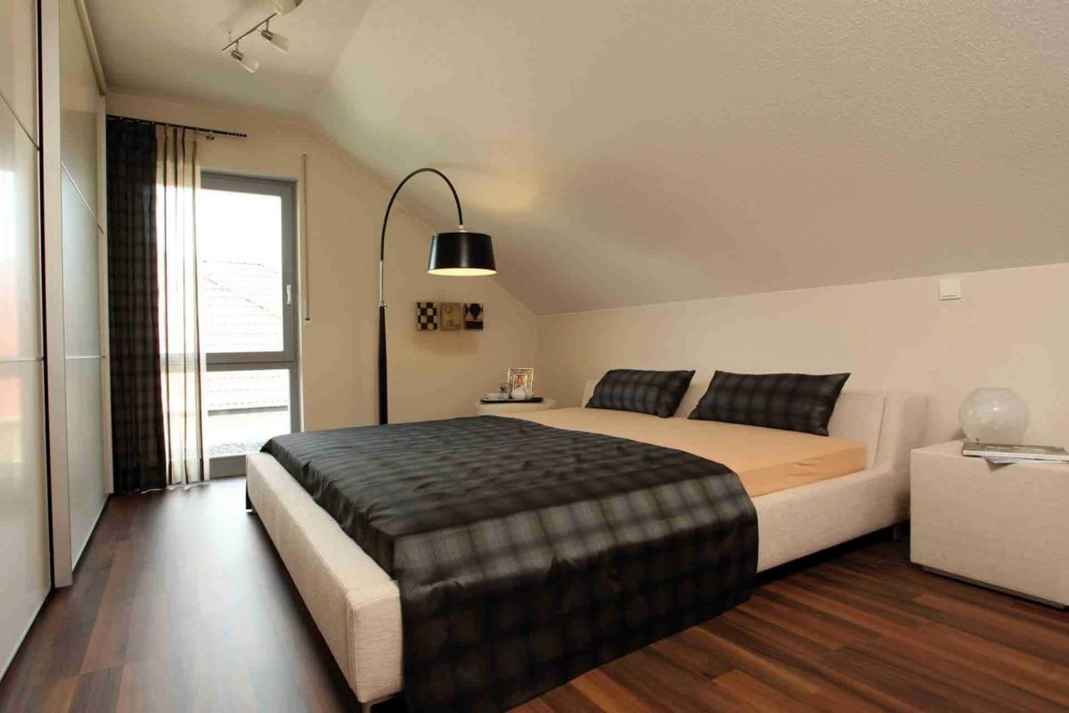 FLAIRplus – Musterhaus Marburg - Ein Schlafzimmer mit einem Bett und einem Schreibtisch in einem Raum - Schlafzimmer