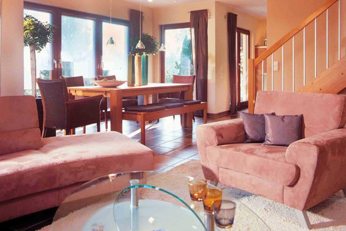 FINO 300 A – Musterhaus Würzburg - Ein Wohnzimmer mit Möbeln und einem Kamin - FingerHaus