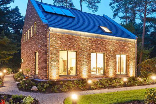 Haus Kaiserberg - Ein großes Backsteingebäude mit Gras vor einem Haus - Gussek Haus