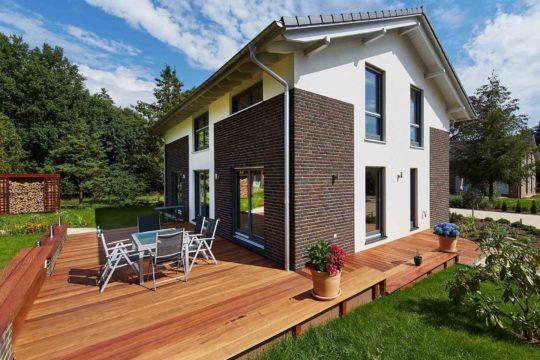 Musterhaus Melanie - Ein großes Backsteingebäude mit Gras vor einem Haus - Haus