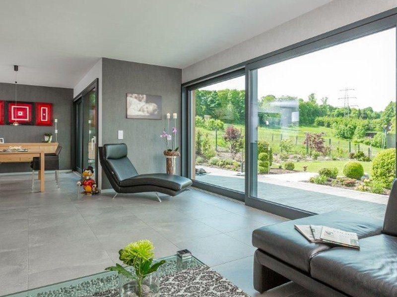 Bauhaus-Villa - Eine Ansicht eines mit Möbeln gefüllten Wohnzimmers und eines großen Fensters - Haus