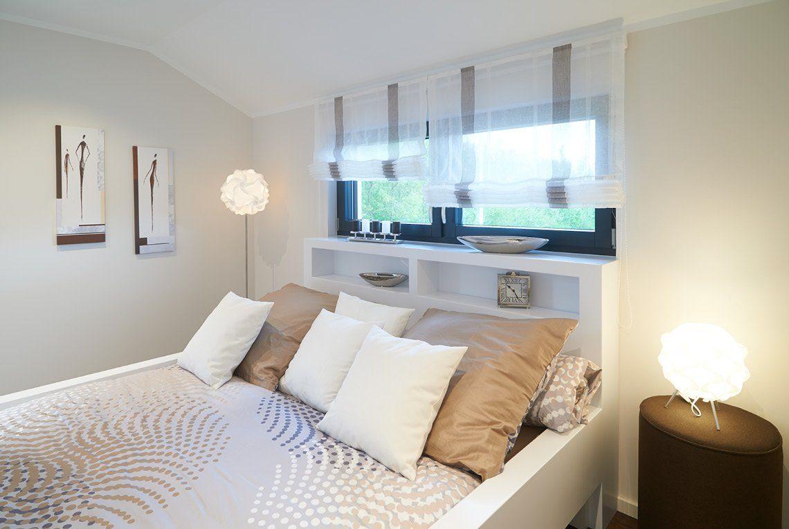 Musterhaus Innovation R - Ein großes weißes Bett in einem Wohnzimmer - Haus