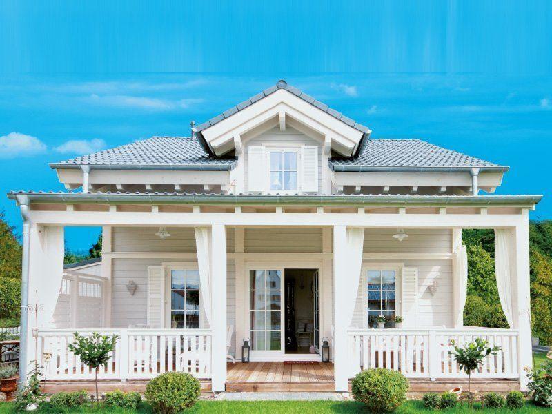 Kleine Traumvilla - Ein großes weißes Gebäude mit Säulen vor einem Haus - Holzhaus