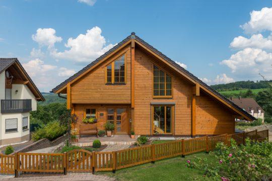 Musterhaus Dhrontalblick - Ein Haus mit einem Holzzaun - Fullwood Wohnblockhaus