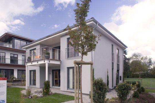 Individuelle Stadtvilla - Ein großes Backsteingebäude mit Gras vor einem Haus - 78259