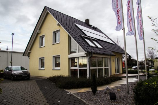 Musterhaus Kamen - Ein Haus, das an der Seite eines Gebäudes geparkt ist - Heinz von Heiden - Musterhaus Kamen