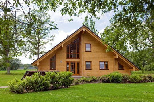 Holzhaus Barkhof - Ein großes Backsteingebäude mit Gras vor einem Haus - Holzhaus