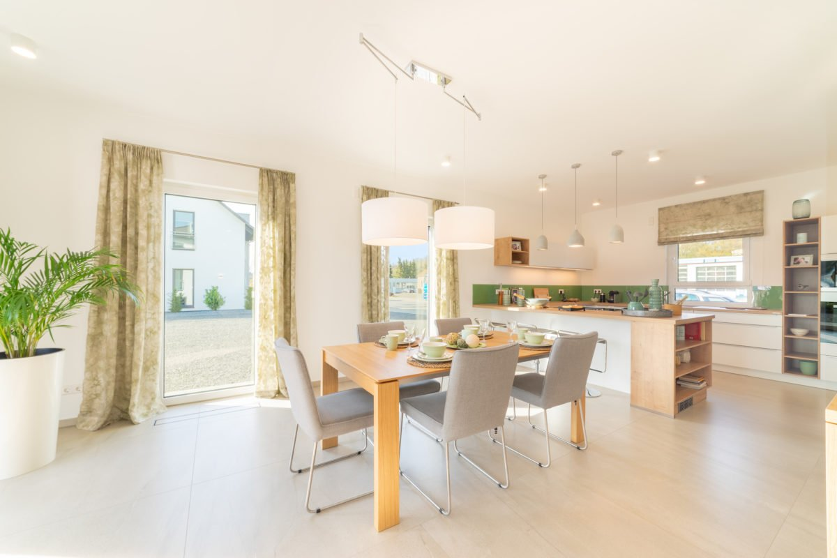 Musterhaus Arnsberg - Ein Wohnzimmer mit Möbeln und einem großen Fenster - Interior Design Services