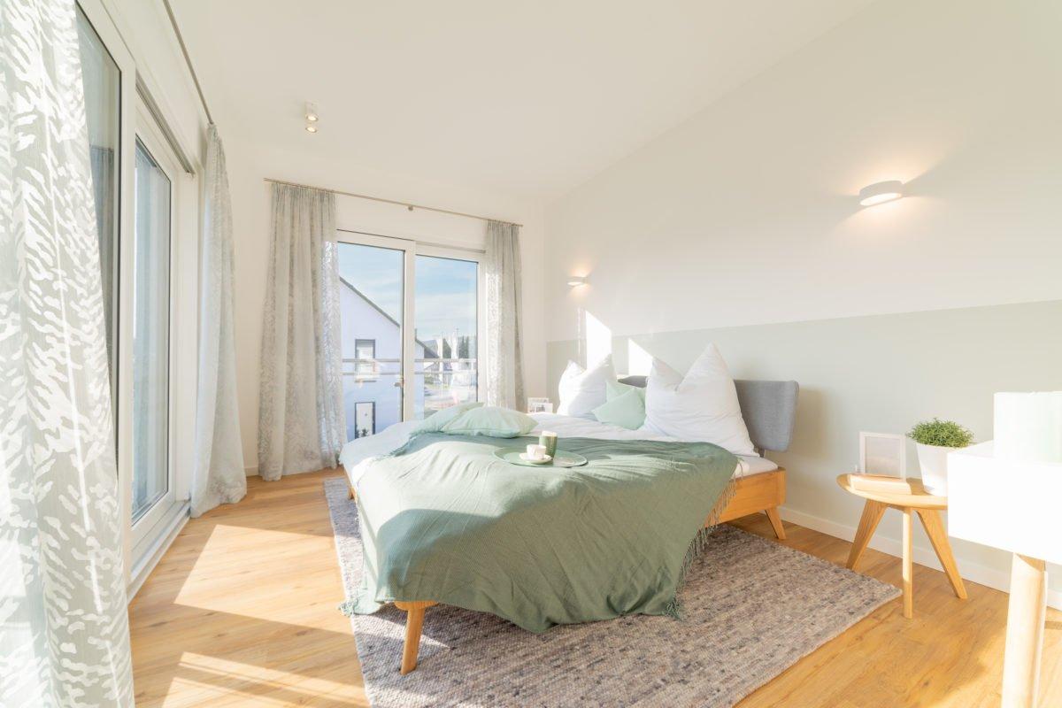 Musterhaus Arnsberg - Ein Wohnzimmer mit Möbeln und einem großen Fenster - Schlafzimmer