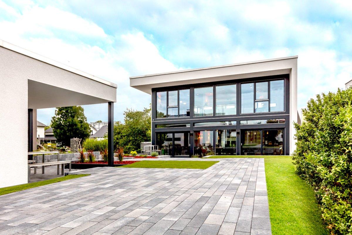 Musterhaus Fusion - Ein großes Backsteingebäude mit Gras und Bäumen - Haus