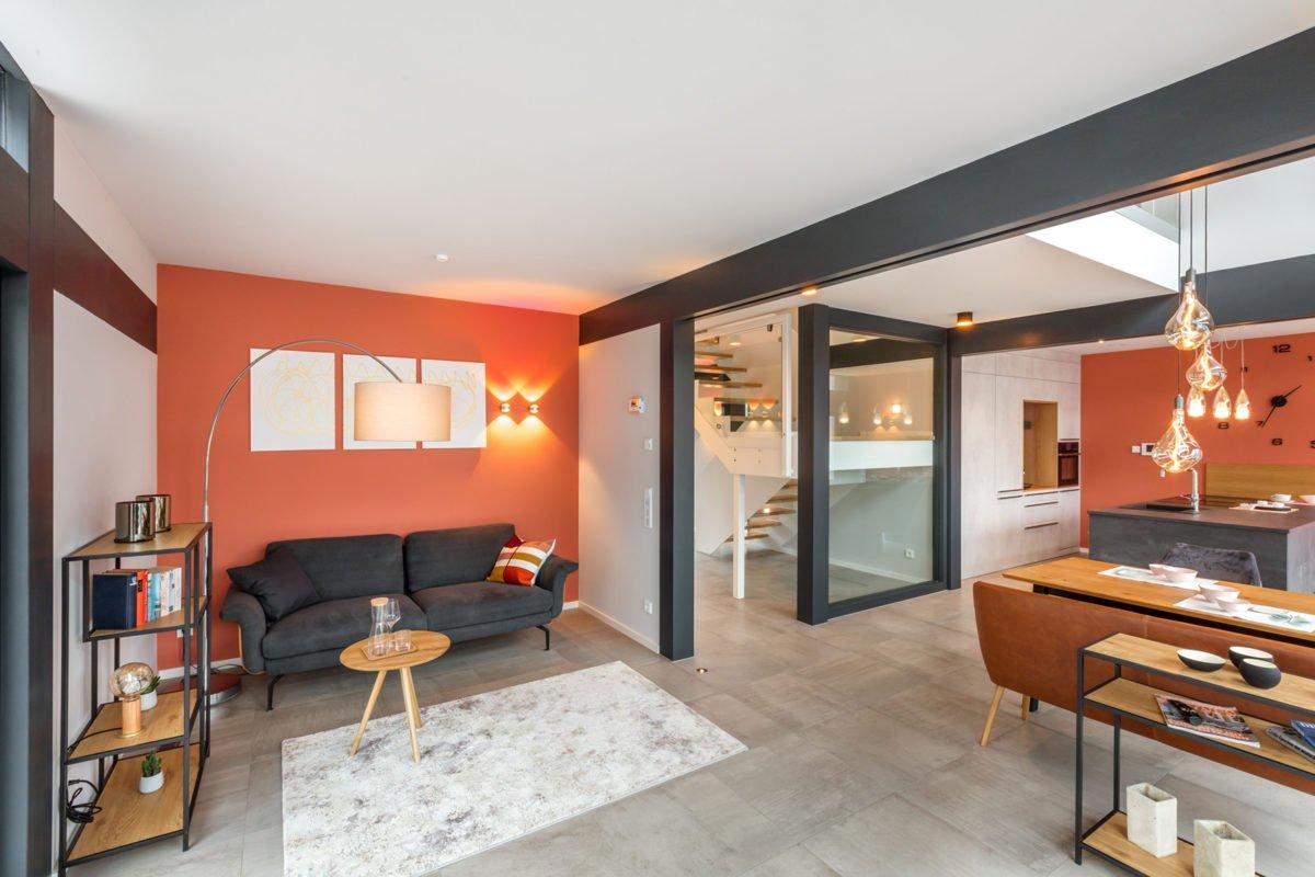 Musterhaus Fusion - Ein Wohnzimmer mit Möbeln und einem Flachbildfernseher - Die Architektur
