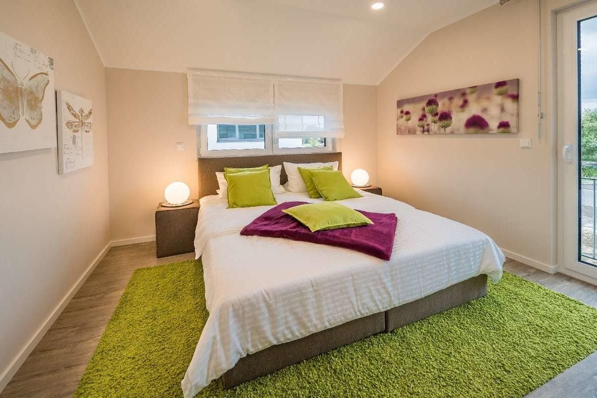 Musterhaus Modena - Ein Schlafzimmer mit einem Bett und einem Spiegel - Schlafzimmer