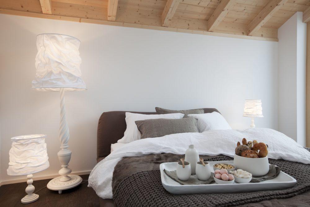 Musterhaus Suhr - Ein Schlafzimmer mit einem Bett und einem Tisch - Home Expo Suhr