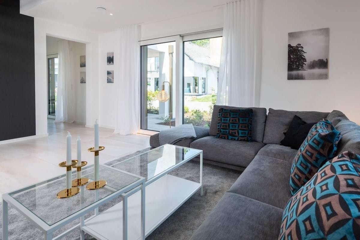 Musterhaus Victoria - Ein Wohnzimmer mit Möbeln und einem großen Fenster - Haus