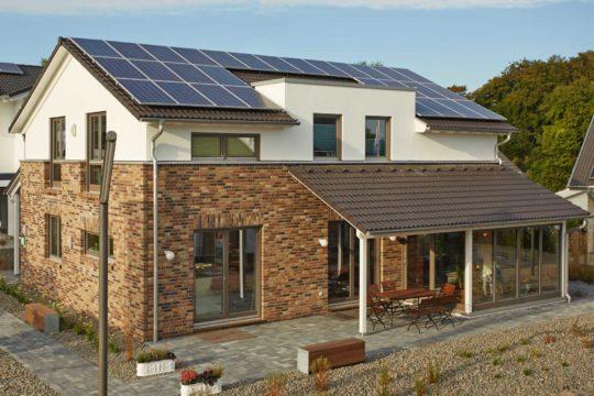 Plus-Energiehaus Isabella - Ein Haus, das an der Seite eines Gebäudes geparkt ist - Gussek Haus