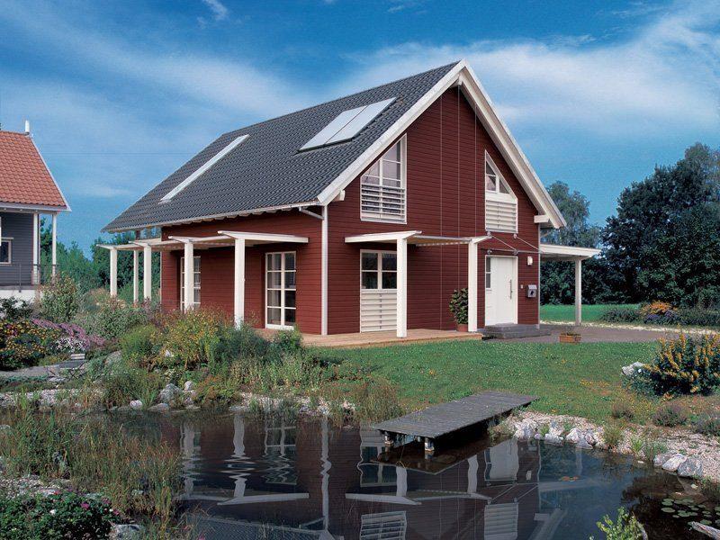 Skandinavische Variante - Ein großes Backsteingebäude mit Gras vor einem Haus - Holzhaus