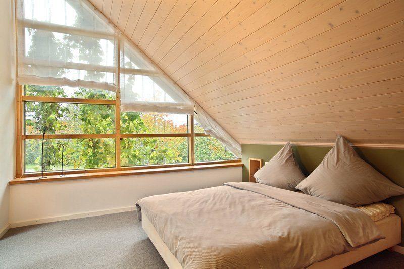 Skandinavische Variante - Ein Schlafzimmer mit einem großen Bett neben einem Fenster - Schlafzimmer