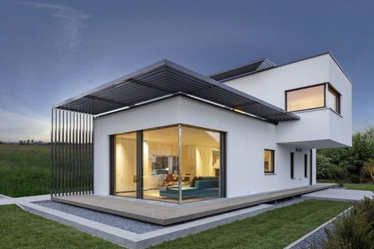Musterhaus Fine - Ein großes Backsteingebäude mit Gras vor einem Haus - Haus