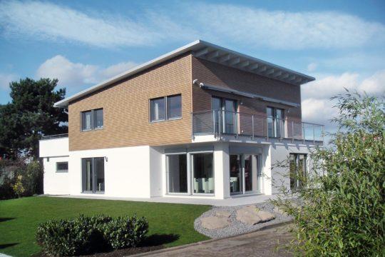 Plan E 15-214.1 - Ein großes Backsteingebäude mit Gras vor einem Haus - Musterhauszentrum Mülheim-Kärlich