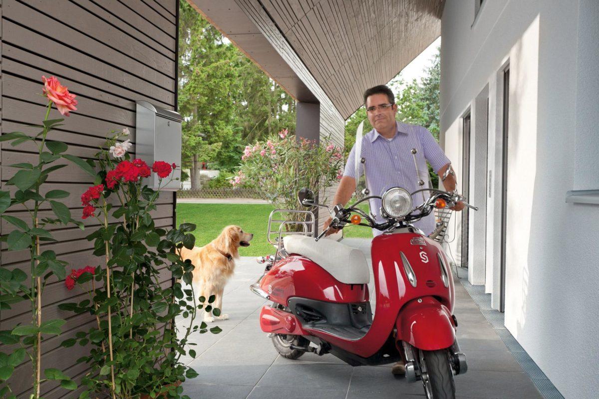 Plan E 15-140.1 - Eine Person, die ein rotes Motorrad fährt und an der Seite eines Gebäudes geparkt ist - SchwörerHaus KG Musterhaus Helmstorf