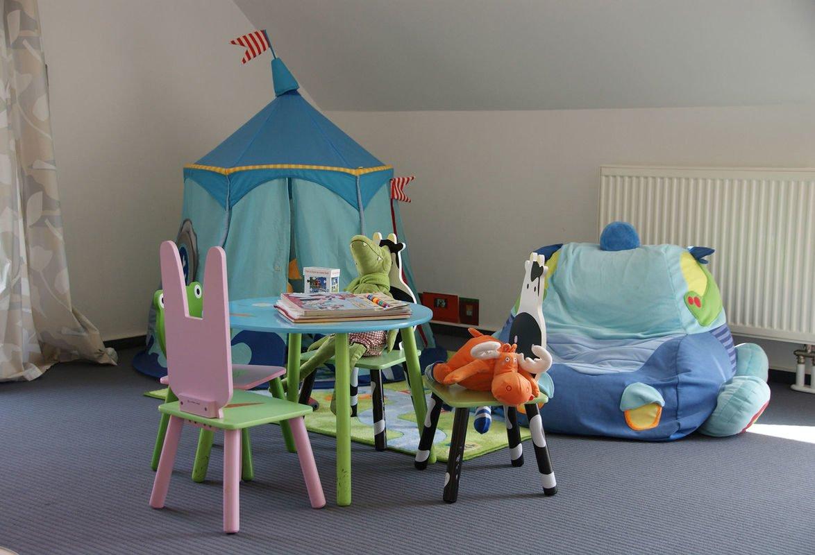 Musterhaus Bad Vilbel - Ein Schlafzimmer mit einem Bett und einem Stuhl in einem Raum - Bad Vilbel