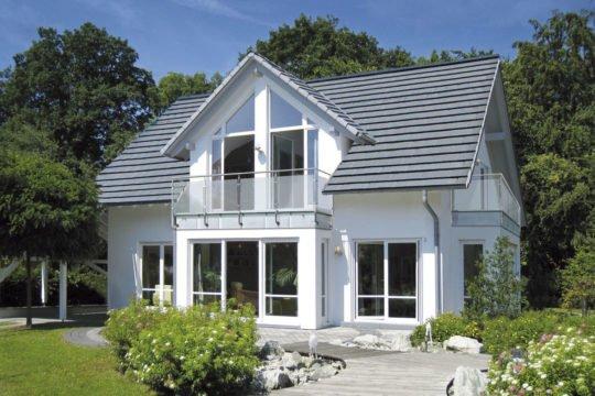 Musterhaus Bad Vilbel - Ein haus mit büschen vor einem gebäude - Fertighaus Weiss