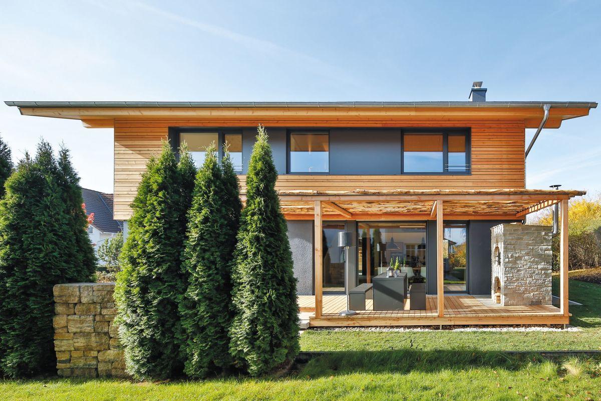 Musterhaus Poing - Ein großes Backsteingebäude mit Gras vor einem Haus - Holzhaus