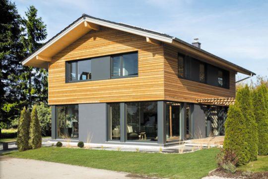 Musterhaus Poing - Ein großes Backsteingebäude mit Gras vor einem Haus - Haus