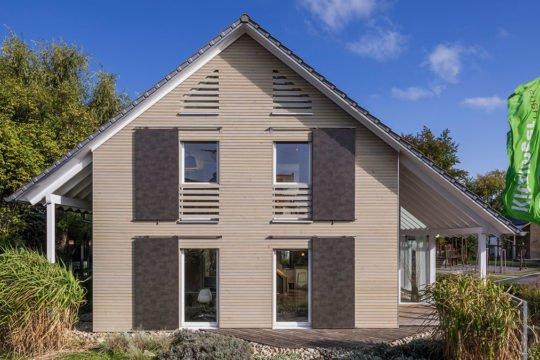 Musterhaus Fellbach - Ein Haus mit Büschen vor einem Backsteingebäude - Abstellgleis