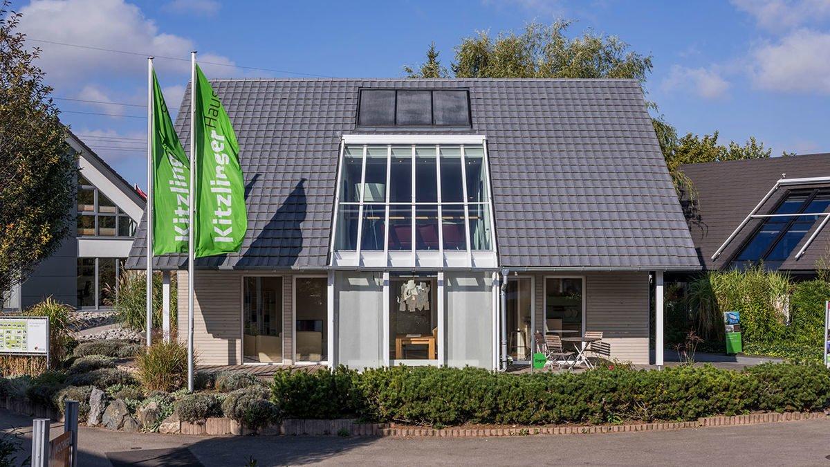 Musterhaus Fellbach - Ein Haus mit Bäumen vor einem Gebäude - OKAL GmbH