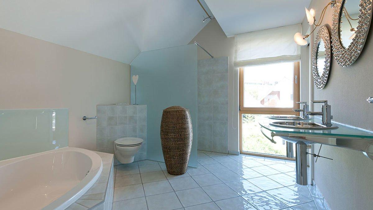 Musterhaus Fellbach - Eine große weiße Wanne neben einem Waschbecken - Bad