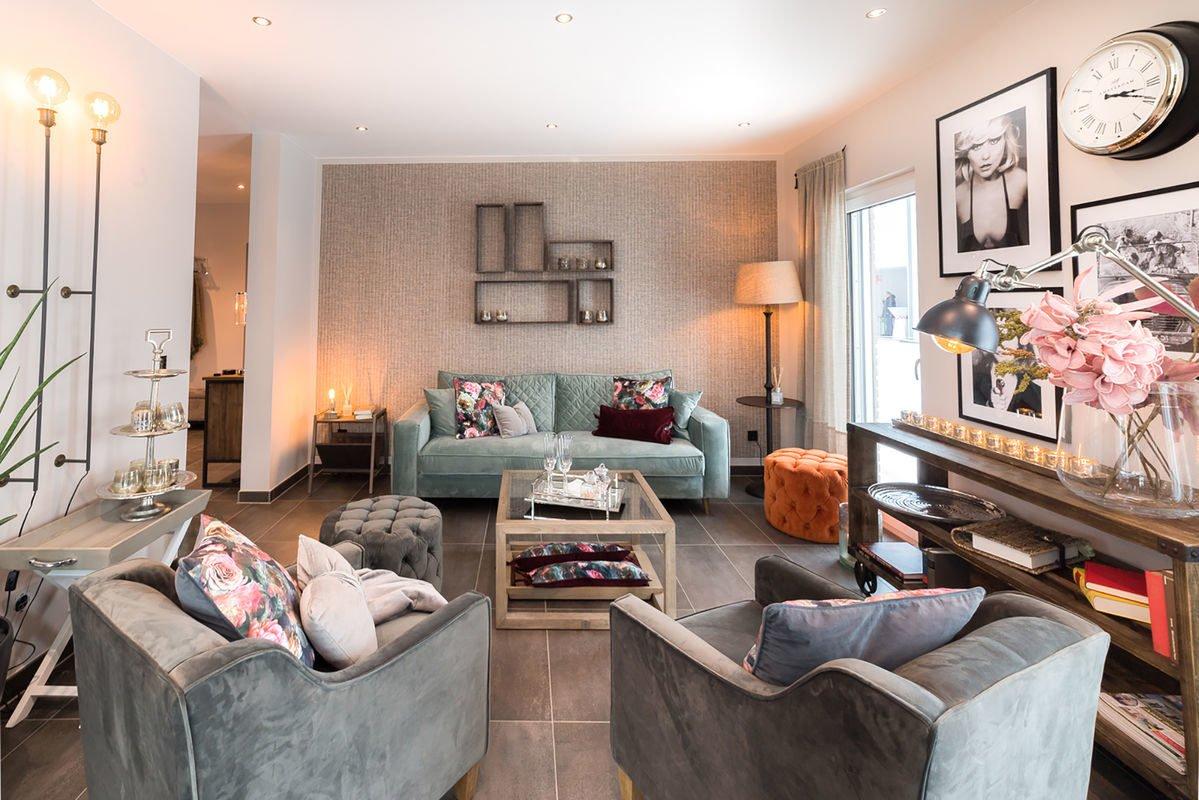 Musterhaus Medley 3.0 - Ein Wohnzimmer mit Möbeln und einem Kamin - FingerHaus
