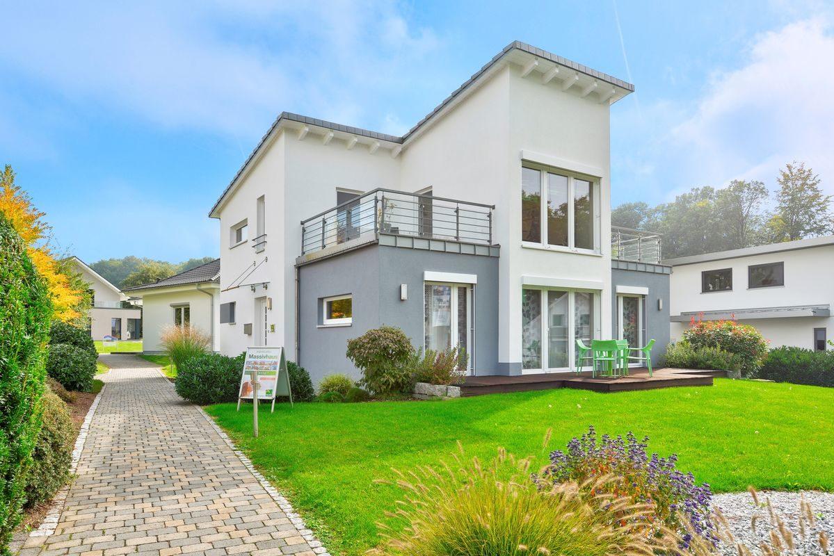 Musterhaus Frankfurt - Ein großes Backsteingebäude mit Gras vor einem Haus mit Southfork Ranch im Hintergrund - Karlsbad