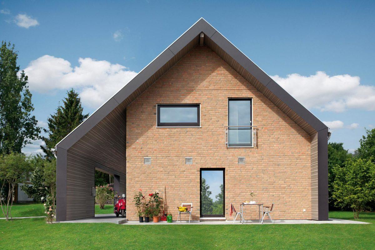 Plan E 15-140.1 - Ein großes Backsteingebäude mit Gras vor einem Haus - SchwörerHaus KG Musterhaus Helmstorf