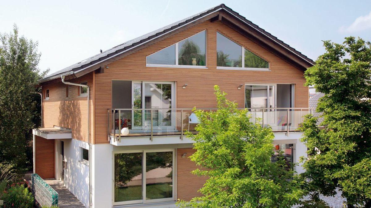 Plan E15-206.1 - Ein Haus mit Bäumen vor einem Backsteingebäude - SchwörerHaus KG Musterhaus Fellbach