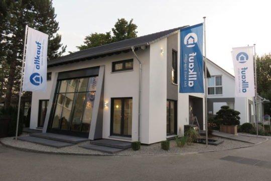 Trendline 1 - Ein Haus mit einem Schild am Straßenrand - allkauf haus - Musterhaus Poing