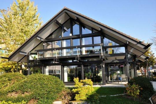 HUF HAUS Musterhaus Stuttgart - Ein haus mit büschen vor einem gebäude - Haus
