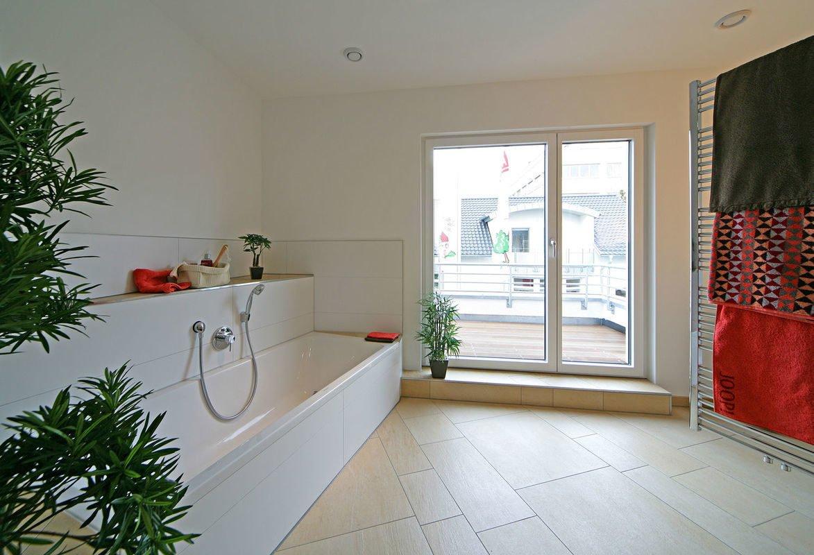 Plus-Energie-Haus Emotion - Ein Wohnzimmer mit Möbeln und einem großen Fenster - Haus