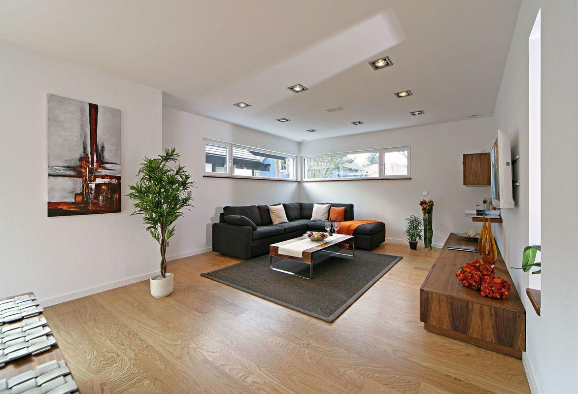 Plus-Energie-Haus Emotion - Ein Wohnzimmer mit Möbeln und einem Tisch - Fertighaus