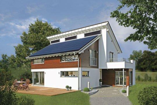 Plus-Energie-Haus Emotion - Ein großes Backsteingebäude mit Gras vor einem Haus - Haus