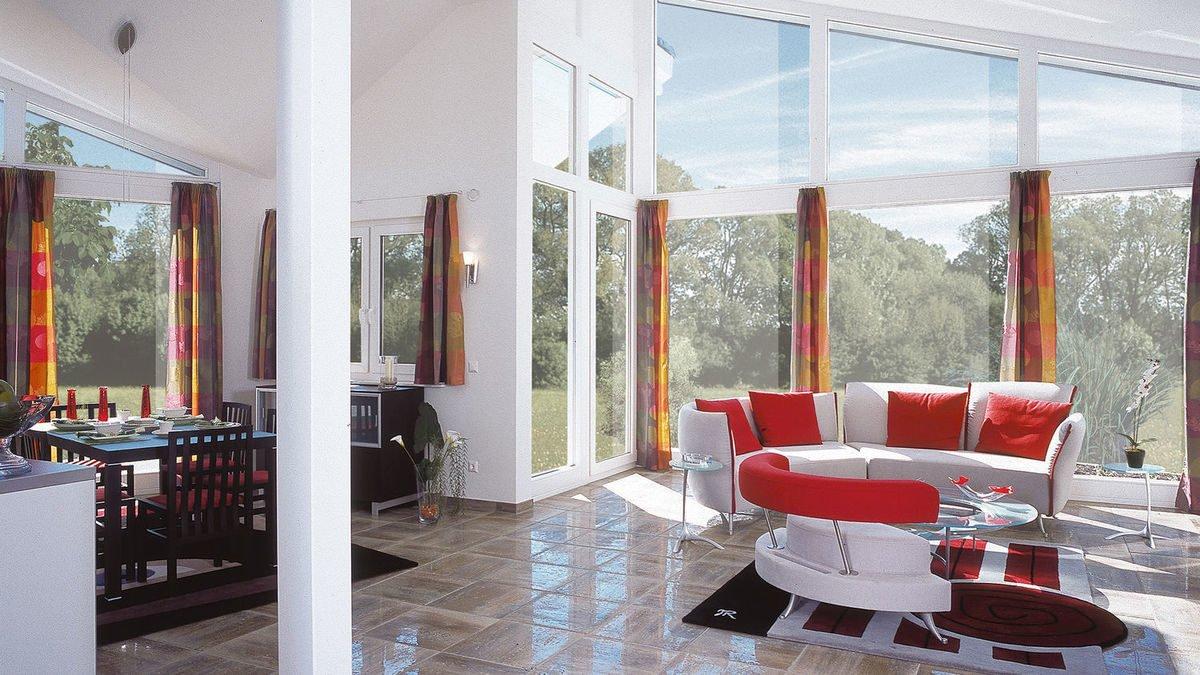 Evolution Königstein - Ein Wohnzimmer mit Möbeln und einem großen Fenster - Bien-Zenker