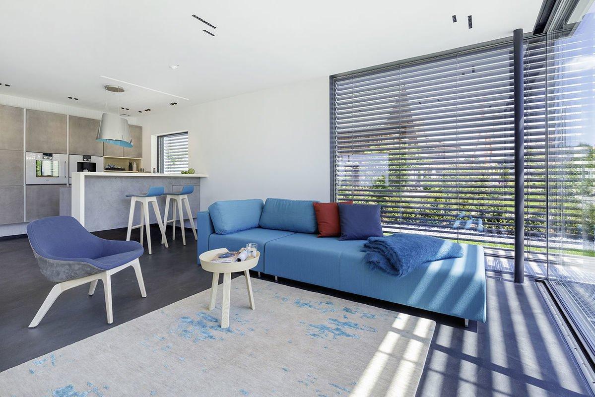 Musterhaus Fine - Ein Wohnzimmer mit Möbeln und einem blauen Stuhl - Interior Design Services