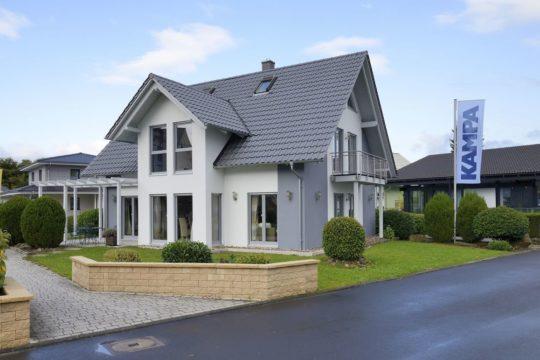 Musterhaus Bad Vilbel - Ein großes Backsteingebäude mit Gras vor einem Haus - Haus