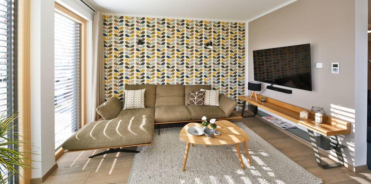 Musterhaus Poing - Ein Wohnzimmer mit Möbeln und einem großen Fenster - Haus zeigen