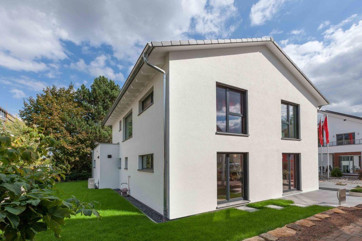 Musterhaus Fellbach - Ein großes Backsteingebäude mit Gras vor einem Haus - Haus