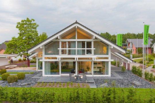 HUF HAUS Musterhaus Frankfurt - Ein Haus mit Bäumen im Hintergrund - Huf Haus